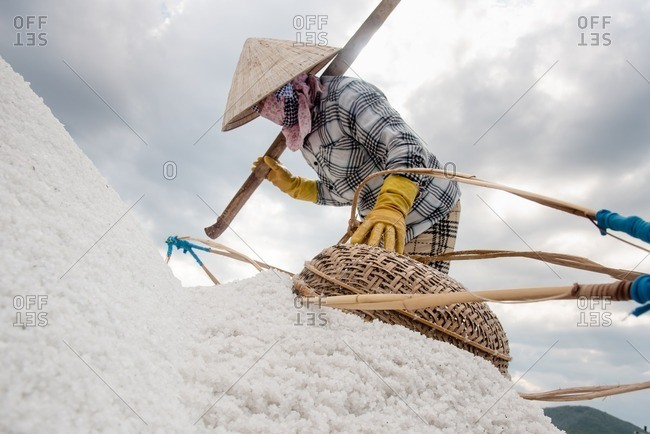 Woman pouring salt at salt farm