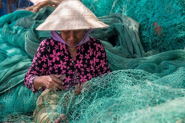 Nha Trang, Vietnam - September 6, 2016: Vietnamese woman stitching up fishing net