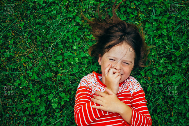 Girl giggling while lying in grass