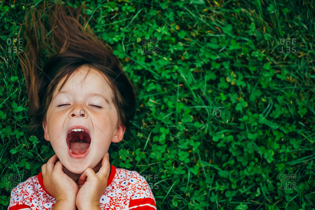 Girl yelling lying in grass