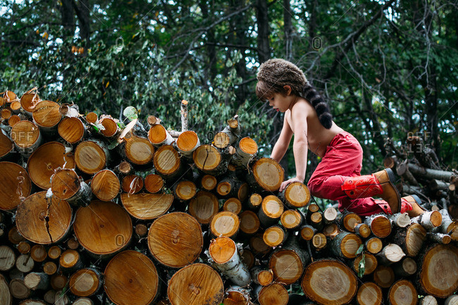 Young boy climbing on a wood pile