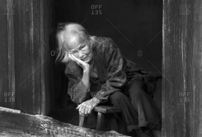 Guilin, China - September 28, 2009: Portrait of an old lady looking out of her house