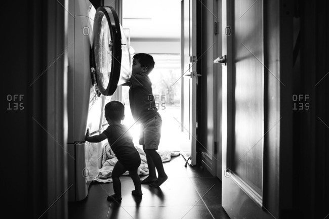 Boy and toddler by laundry machine