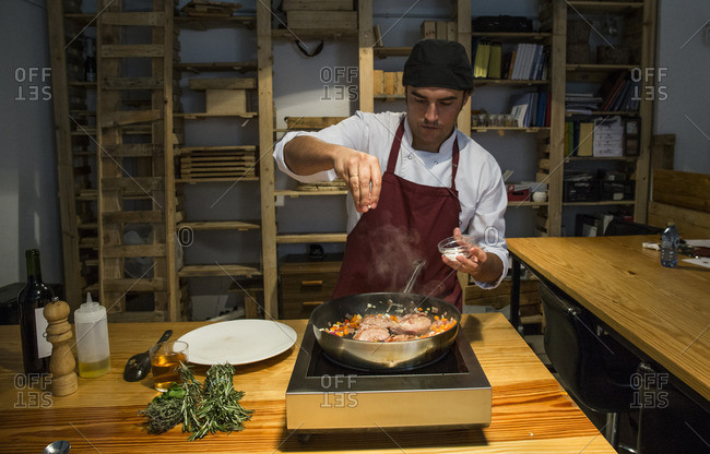 Man pouring salt on beef cheeks in a pan with sautŽed vegetables