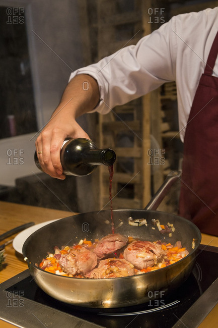 Man pouring wine on beef cheeks in a pan with sautŽed vegetables