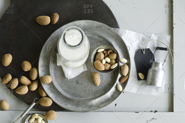 Glass bottle of homemade almond milk and almonds