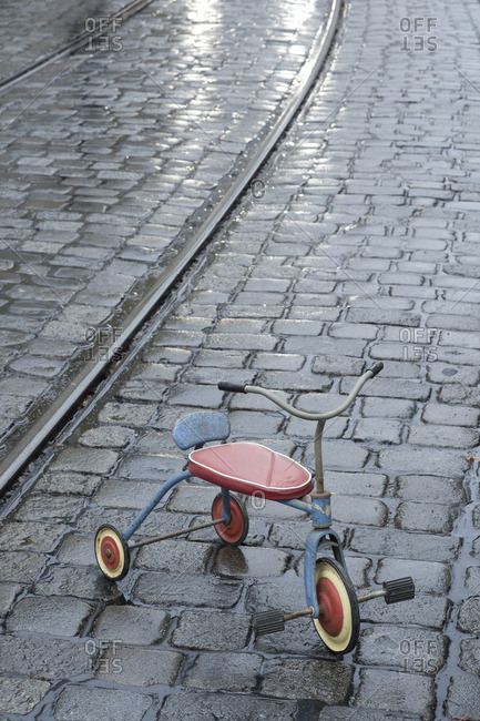 Old children's tricycle on rainy pavement