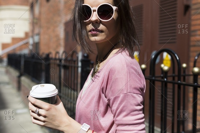 Fashionable young woman with coffee to go wearing pink sunglasses and cardigan