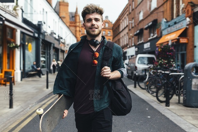 Ireland- Dublin- portrait of young man with skateboard walking on the street