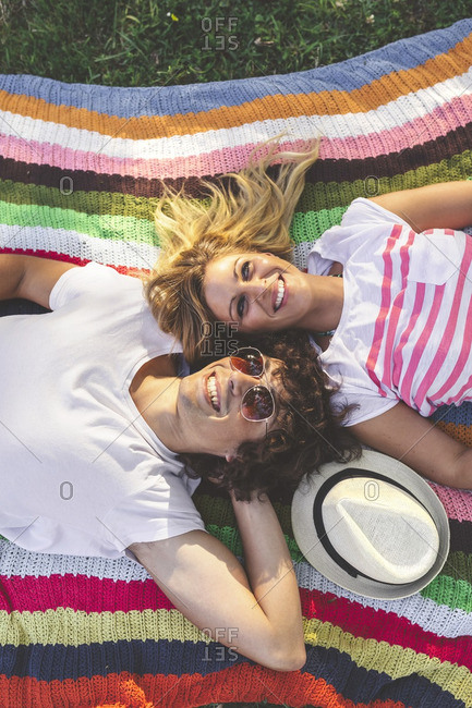Happy young couple lying on blanket in park