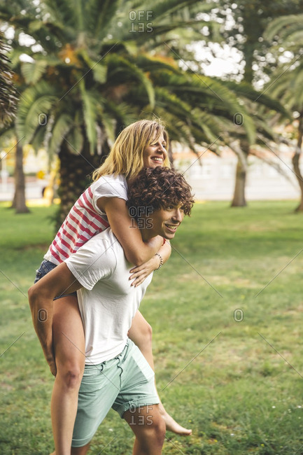Young man giving girlfriend piggyback ride in park