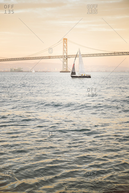 USA- San Francisco- Sailing boat against Bay bridge at sunset