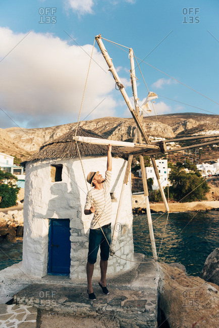 Greece- Amorgos- Aegialis- man holding the  blades of wind mill