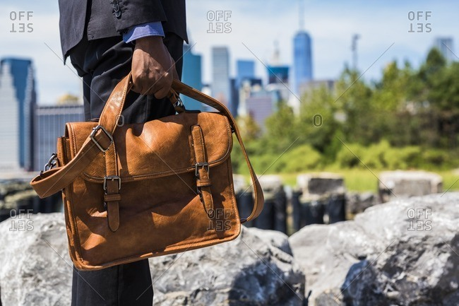 USA- Brooklyn- businessman with briefcase standing in front of Manhattan skyline- partial view
