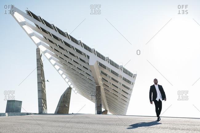 Businessman walking at solar panels