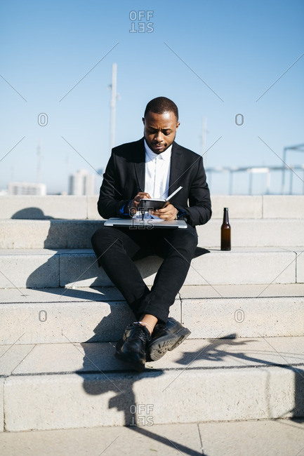 Businessman sitting on stairs with bottle of beer- notebook and laptop