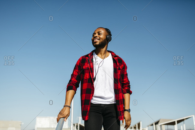 Smiling man listening to music with headphones outside