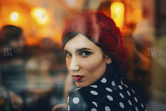 Portrait of young woman wearing red hat looking through window of a pub in the evening
