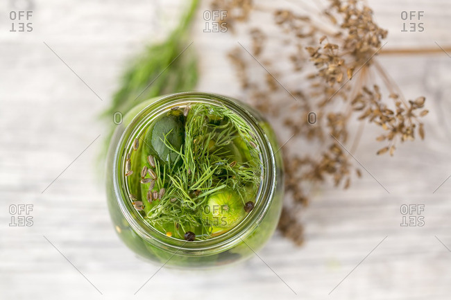 Pickled gherkins in jar with mustard seeds- fennel seeds and dill