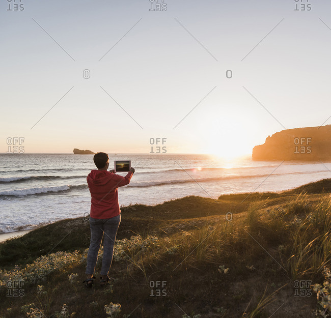 France- Bretagne- Croon peninsula- woman at the coast at sunset taking picture with tablet