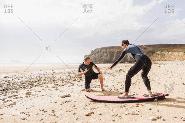 France- Bretagne- Croon peninsula- man teaching woman surfing on beach