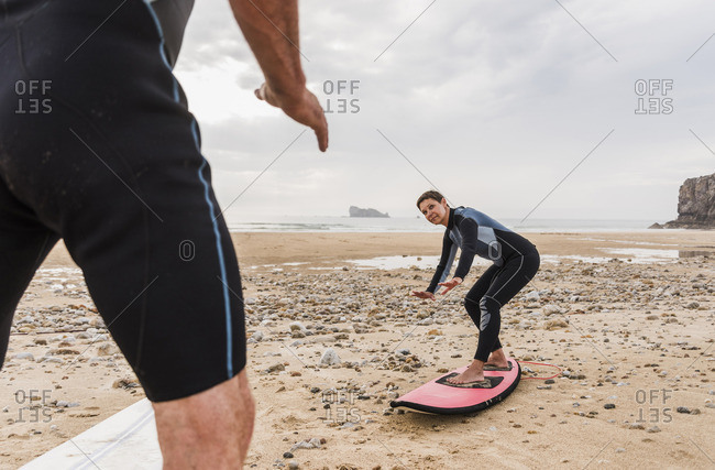 France- Bretagne- Croon peninsula- man teaching woman surfing on beach