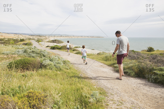 Man and sons walking on coastal trail