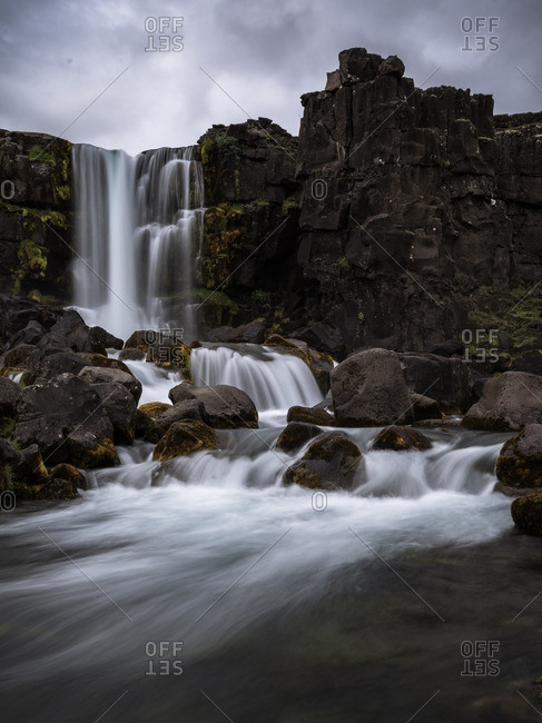 Water cascading over black basaltic rocks in Pingvellir National Park, Iceland