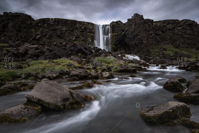 Oxararfoss Waterfall under cloudy skies, Pingvellir National Park, Iceland