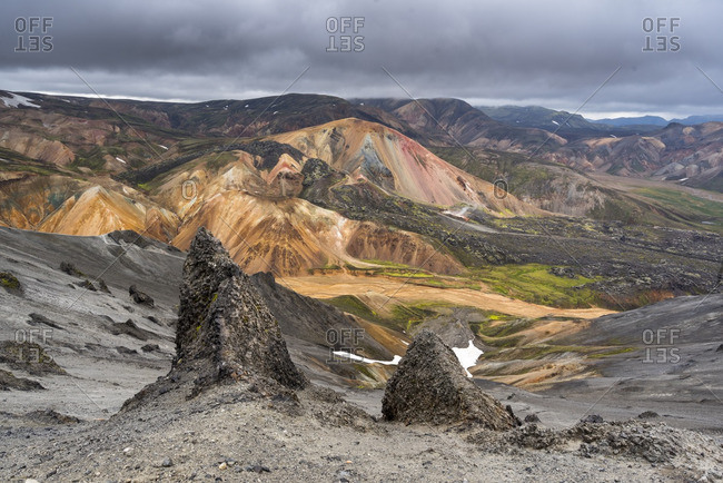 Volcanic rock formations before colorful hills in Fjallabak Nature Reserve, Iceland
