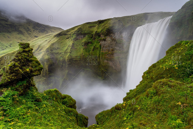 Skogafoss seen from mossy cliffs in Iceland