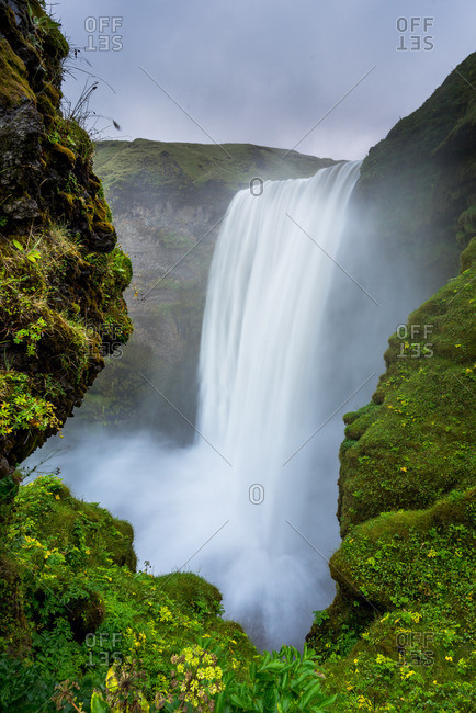 Misty Skogafoss waterfall cascades over the former coastline of Iceland