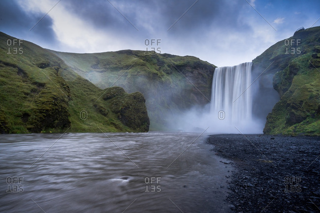 Skogafoss waterfall cascades over cliffs into misty basin