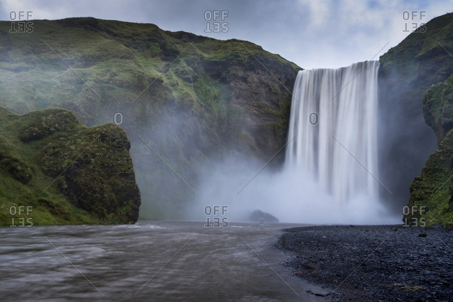View of misty Skogafoss waterfall from below the cliffs