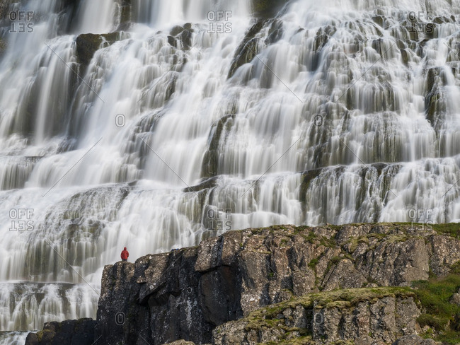 Person in red raincoat gazing at waterfall in Iceland