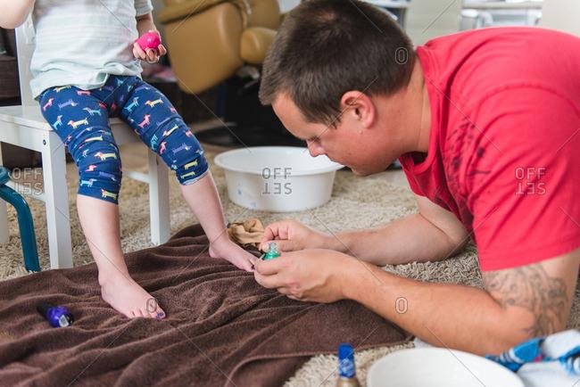 Dad painting toenails of toddler daughter