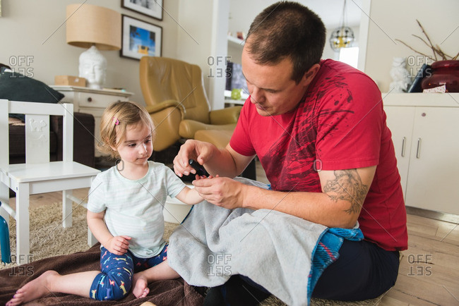 Man painting fingernails of toddler daughter