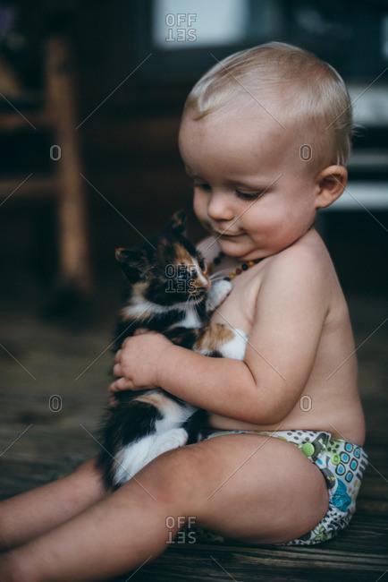 Baby petting a kitten