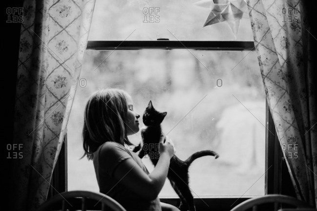Girl holding a kitten in front of a window