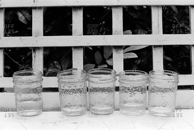 Mason jars with water on a bench