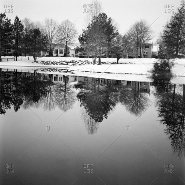 Trees and houses in snow reflected in a pond