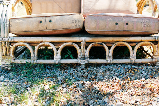 Legs and cushions of a vintage patio sofa on gravel