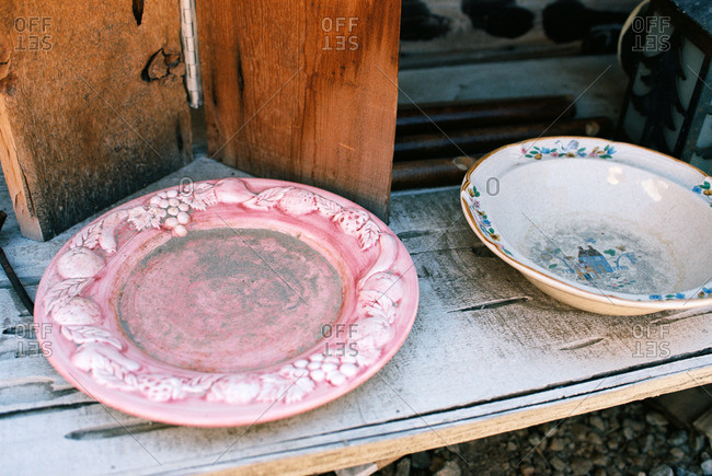 Vintage plates covered in dirt on a wooden bench