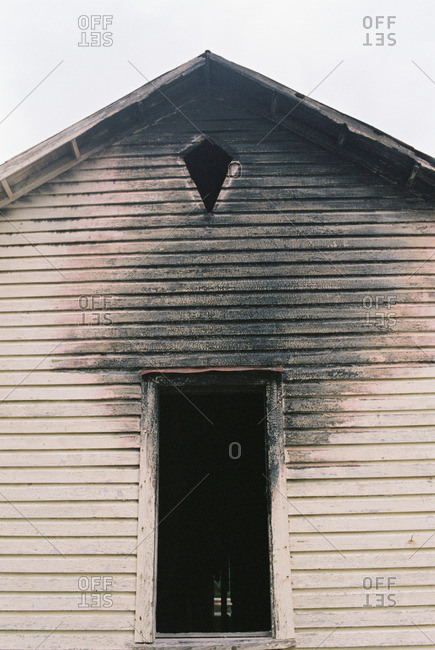 Open window and siding on a fire-damaged house