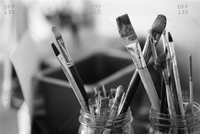 Various used paintbrushes in glass jars