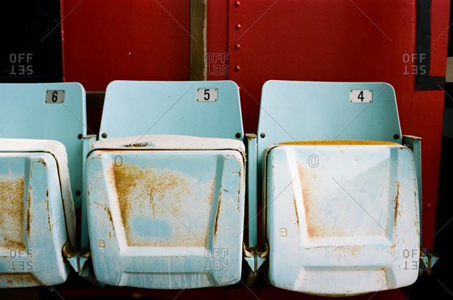 Row of old stadium seats with rusted bottoms