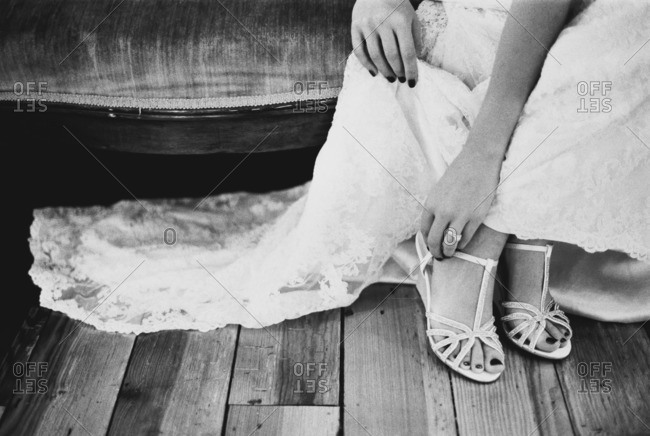 Bride sitting on a vintage couch strapping her shoes