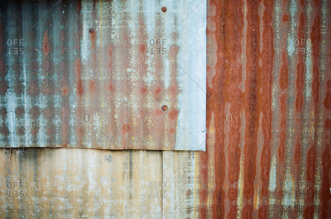 Overlapping sheets of rusted corrugated tin