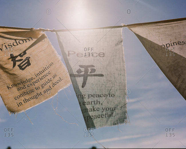 Prayer flags with wisdom, peace and happiness fluttering in a breeze