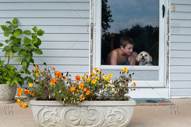 Boy with small white dog at front door
